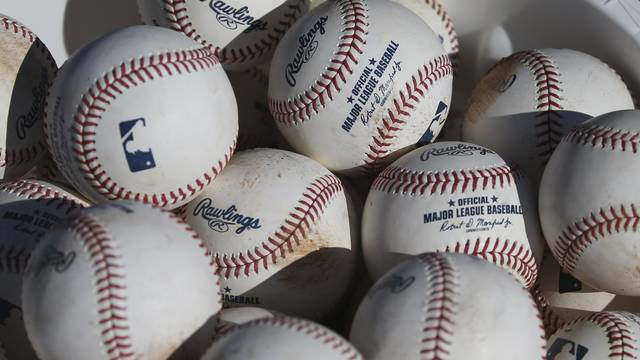 """FILE - In this Feb. 14, 2020, file photo, baseballs occupy a bucket after use during fielding practice during spring training baseball workouts for pitchers and catchers at Cleveland Indians camp in Avondale, Ariz. Major League Baseball is suspending all political contributions in the wake of last week's invasion of the U.S. Capitol by a mob loyal to President Donald Trump, joining a wave of major corporations rethinking their efforts to lobby Washington. """"In light of the unprecedented events last week at the U.S. Capitol, MLB is suspending contributions from its Political Action Committee pending a review of our political contribution policy going forward,"""" the league said in a statement to The Associated Press on Wednesday, Jan. 13, 2021. (AP Photo/Ross D. Franklin, File)"""