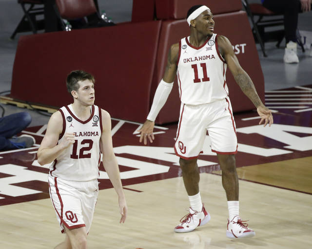 Oklahoma guards Austin Reaves (12) and De'Vion Harmon (11) react after beating Kansas in an NCAA college basketball game in Norman, Okla., Saturday, Jan. 23, 2021. (AP Photo/Garett Fisbeck)