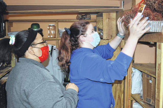Wilmington College students Savannah Manson, left, and Hannah Rammel help organize the storage area in the Clinton County Homeless Shelter's Matrka Family House.