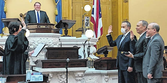 State Senator Bob Peterson (R-Washington C.H.) takes the oath of office for the 134th General Assembly. Peterson is pictured in the middle of the three men on the right.
