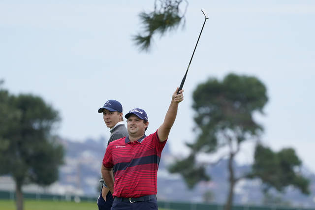 Patrick Reed, right, signals for an official in front of Carlos Ortiz, of Mexico, on the 16th hole on the South Course during the final round of the Farmers Insurance Open golf tournament at Torrey Pines, Sunday, Jan. 31, 2021, in San Diego. (AP Photo/Gregory Bull)