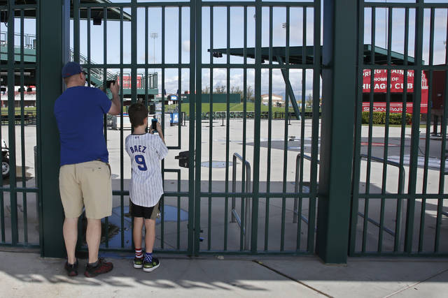 FILE - Cubs fans take photos through the locked gates at Sloan Park, the spring training site of the Chicago Cubs, in Mesa, Ariz., after Major League Baseball suspended the rest of its spring training game schedule because of the coronavirus outbreak, in this Friday, March 13, 2020, file photo. The Cactus League and Arizona community leaders have asked Major League Baseball to delay the start of spring training due to coronavirus concerns just over three weeks before pitchers and catchers are supposed to report. The Cactus League made the request in a letter to Baseball Commissioner Rob Manfred obtained by The Associated Press on Monday, Jan. 25, 2021. (AP Photo/Sue Ogrocki, File)