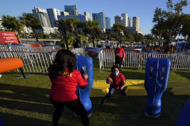 Anaja Brackett, center, runs with a football at the NFL Experience for Super Bowl LV Friday, Jan. 29, 2021, in Tampa, Fla. (AP Photo/David J. Phillip)