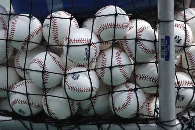 FILE - In this July 3, 2020, file photo, balls marked with Cactus League spring training logos are in a basket during Kansas City Royals baseball practice at Kauffman Stadium in Kansas City, Mo. Major League Baseball has slightly deadened its baseballs amid a years-long surge in home runs. MLB anticipates the changes will be subtle, and a memo to teams last week cites an independent lab that found the new balls will fly 1 to 2 feet shorter on balls hit over 375 feet. (AP Photo/Charlie Riedel, File)