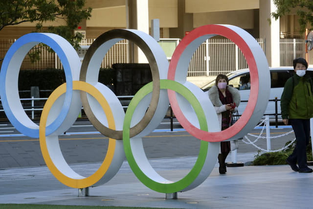 People walk past the Olympic rings in Tokyo Tuesday, Feb. 2, 2021. Pressure is building on Japanese organizers and the IOC to explain exactly how they plan to hold the Tokyo Olympics in the midst of a pandemic. (AP Photo/Koji Sasahara)