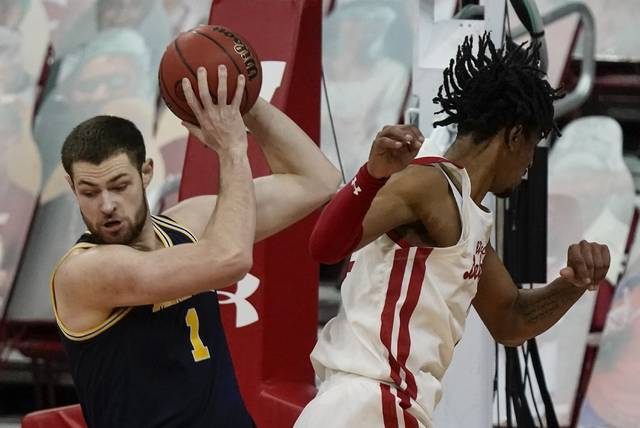 Michigan's Hunter Dickinson gets past Wisconsin's Aleem Ford during the first half of an NCAA college basketball game Sunday, Feb. 14, 2021, in Madison, Wis. (AP Photo/Morry Gash)