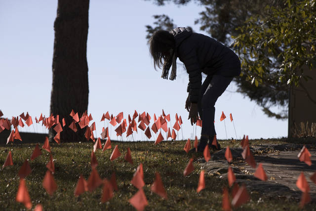 Cindy Pollock does maintenance on the construction flags in her front yard in Boise, Idaho, on Wednesday, Feb. 10, 2021. Pollock began planting the tiny flags across her yard — one for each of the more than 1,800 Idahoans killed by COVID-19 — the toll was mostly a number. Until two women she had never met rang her doorbell in tears, seeking a place to mourn the husband and father they had just lost. (AP Photo/Otto Kitsinger)