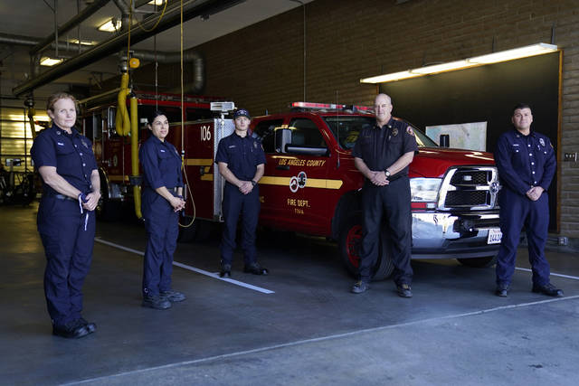 From left, fire Truck Captain Jeane Barrett, firefighter paramedic Sally Ortega, engine probationary firefighter Cole Gomoll, Battalion Chief Dean Douty, and Engine Captain Joe Peña, all first responders from Los Angeles County Fire Department - Station 106, pose for a photo at their station Friday, Feb. 26, 2021, in Rancho Palos Verdes, Calif, a suburb of Los Angeles. The crew responded to the scene of a vehicle crash involving golfer Tiger Woods on Tuesday. (AP Photo/Ashley Landis)
