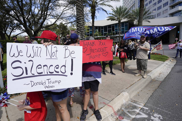 Trump supporters hold signs and wave to motorists outside the convention center at the Conservative Political Action Conference (CPAC) Saturday, Feb. 27, 2021, in Orlando, Fla. (AP Photo/John Raoux)