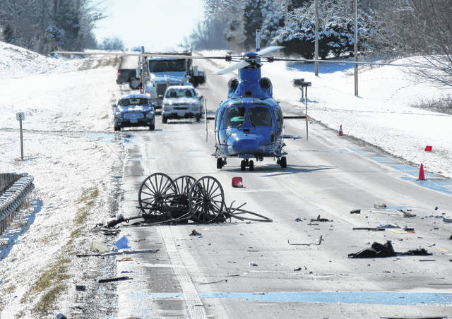 The wreckage of an Amish buggy rests on the roadway of U.S. 62 in front of a CareFlight helicopter from Dayton's Miami Valley Hospital. The driver of the buggy was airlifted with undisclosed injuries following the crash Tuesday afternoon between the buggy and another vehicle.