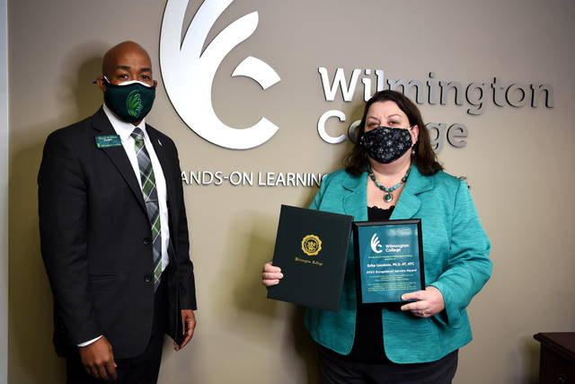 WC President Trevor Bates presents Erika Goodwin with the Board of Trustees' Exceptional Leadership Award during Friday's winter meeting.