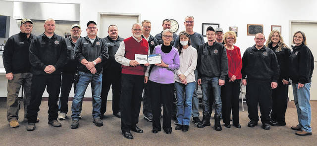 Shown are, from left: Modern Woodmen representative Dan Mayo with Ann Norman and Chris Norman; and, back row, Tim Colonel, Kevin Garen, John Irwin, Alan Henderson, Dave Wiseman, Steve Huff, Brent Terrell, Ben Norman, Dustin Irwin, John Johnson, Bev Mayo, Jason Vance, Stacey Kelley and Linda Ruble.