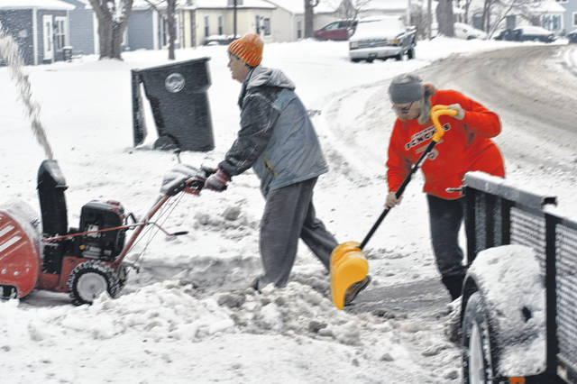 Sisters Brenda, left, and Denise Rankin of D&B Clean Cut Lawn Care remove the fresh powder at a Bernice Street residence.