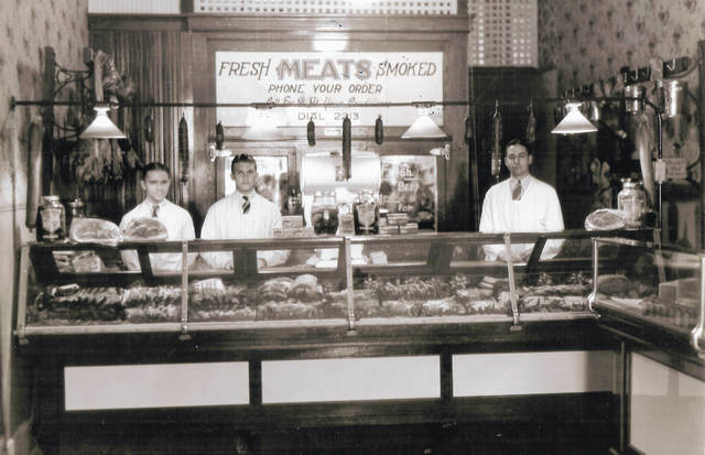 """""""The Market"""" butcher shop on N. South Street — present site of the Wilmington Municipal Building — about 1931. From left are Kenneth Probasco, Richard M. Hiatt, and Sabin Osborn, proprietor. Can you tell us more? Share it at info@wnewsj.com. The photo is courtesy of the Clinton County Historical Society. Like this image? Reproduction copies of this photo are available by calling the History Center. For more info, visit www.clintoncountyhistory.org; follow them on Facebook @ClintonCountyHistory; or call 937-382-4684."""