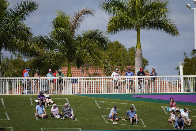 Fans sit in social distance squares during a spring training baseball game with the Minnesota Twins and Boston Red Sox on Sunday, Feb. 28, 2021, in Fort Myers, Fla. (AP Photo/Brynn Anderson)