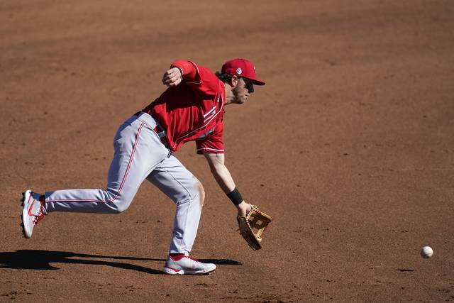 Cincinnati Reds shortstop Kyle Farmer reaches out to scoop up a grounder hit by Cleveland Indians' Billy Hamilton before throwing to first base for the out during the fourth inning of a spring training baseball game Sunday, Feb. 28, 2021, in Goodyear, Ariz. (AP Photo/Ross D. Franklin)
