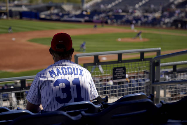 A Chicago Cubs fan watches during the third inning of a spring training baseball game against the San Diego Padres, Monday, March 1, 2021, in Peoria, Ariz. (AP Photo/Charlie Riedel)