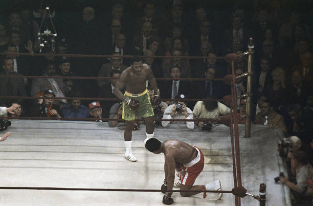 FILE - Boxer Muhammad Ali looks up towards Joe Frazier, center, during a title fight at Madison Square Garden in New York, in this March 8, 1971, file photo. (AP Photo/File)