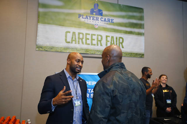 Former NFL player Tony Dixon, left, speaks with an unidentified person at the NFL Player Care Foundation Career Fair in Atlanta on Friday, Feb. 1, 2019. The NFL Player Care Foundation was established in 2007 with the mission of helping former players improve their quality of life. More than 40 national businesses took part in February, including PepsiCo, where Dixon has been on staff since 2009. (AP Photo/Todd Kirkland)