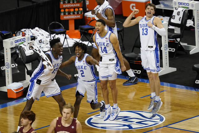 Duke center Mark Williams, left, guard DJ Steward (2) guard Jordan Goldwire (14) and Duke forward Joey Baker (13) celebrate their 86-51 win over Boston College in the first round of the Atlantic Coast Conference tournament in Greensboro, N.C., Tuesday, March 9, 2021. (AP Photo/Gerry Broome)