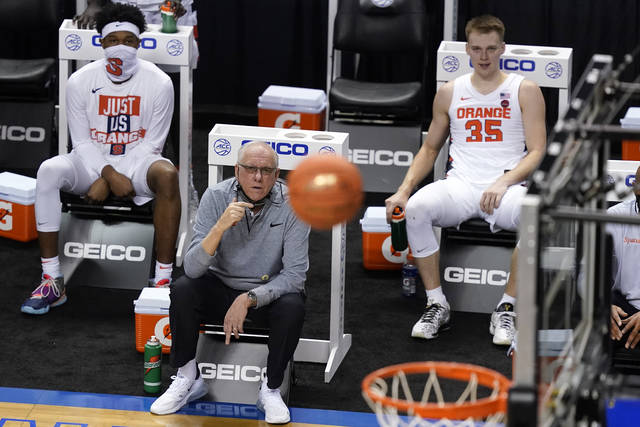 Syracuse head coach Jim Boeheim, seated front, watches a shot as his son guard Buddy Boeheim (35) looks on during the second half of an NCAA college basketball game in the second round of the Atlantic Coast Conference tournament in Greensboro, N.C., Wednesday, March 10, 2021. Syracuse defeated North Carolina State 89-68. (AP Photo/Gerry Broome)