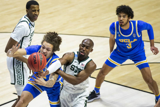 UCLA's Mac Etienne, front left, competes for a rebound with Michigan State's Joshua Langford during the second half of a First Four game in the NCAA men's college basketball tournament, Thursday, March 18, 2021, at Mackey Arena in West Lafayette, Ind. UCLA won 86-80. (AP Photo/Robert Franklin)
