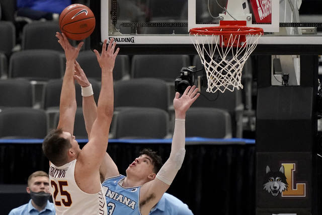 Loyola of Chicago's Cameron Krutwig (25) shoots over Indiana State's Jake LaRavia during the first half of an NCAA college basketball game in the semifinal round of the Missouri Valley Conference men's tournament Saturday, March 6, 2021, in St. Louis. (AP Photo/Jeff Roberson)