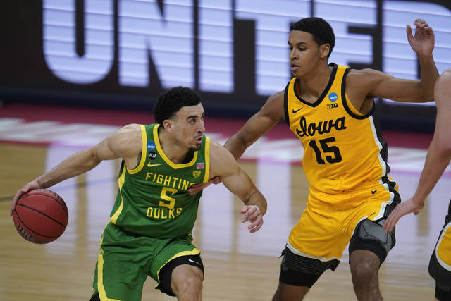Oregon guard Chris Duarte (5) drives on Iowa forward Keegan Murray (15) during the second half of a men's college basketball game in the second round of the NCAA tournament at Bankers Life Fieldhouse in Indianapolis, Monday, March 22, 2021. (AP Photo/Paul Sancya)