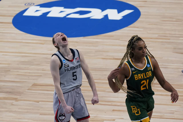 UConn guard Paige Bueckers (5) celebrates the team's win as Baylor guard DiJonai Carrington (21) walks off the court after a college basketball game in the Elite Eight round of the women's NCAA tournament at the Alamodome in San Antonio, Monday, March 29, 2021. (AP Photo/Eric Gay)