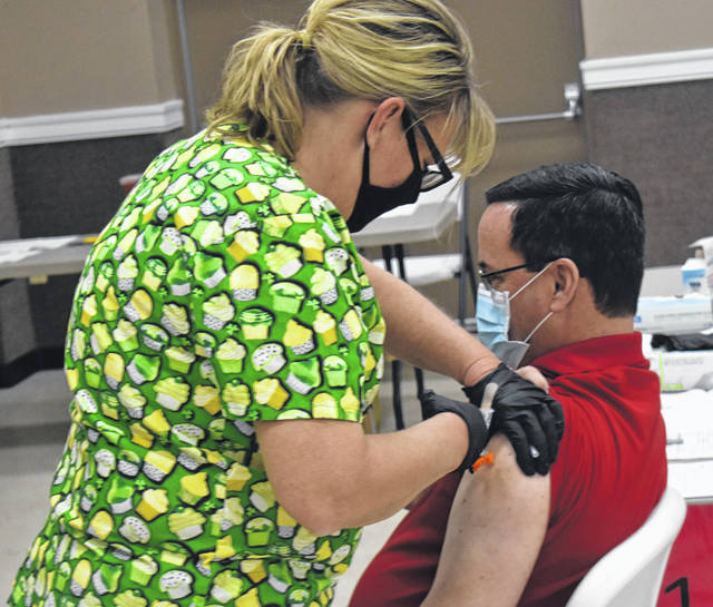 Susan Jacobs, one of the many volunteers of the Clinton County Medical Reserve Corps, administers the COVID-19 vaccine to Mike Williams on Wednesday at the Expo Center at the Clinton County Fairgrounds.
