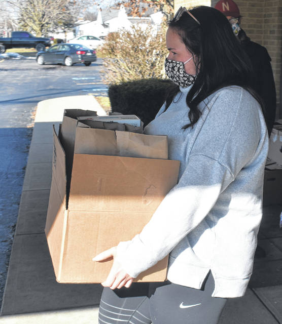 Delaney Roberts brings out a box of food for a local resident during Faith Lutheran Church in Wilmington's open food pantry on Wednesday.
