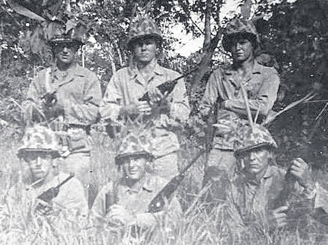 Standing, center, at Guadalcanal in the Pacific Theater is US Marine Bob Caldwell.