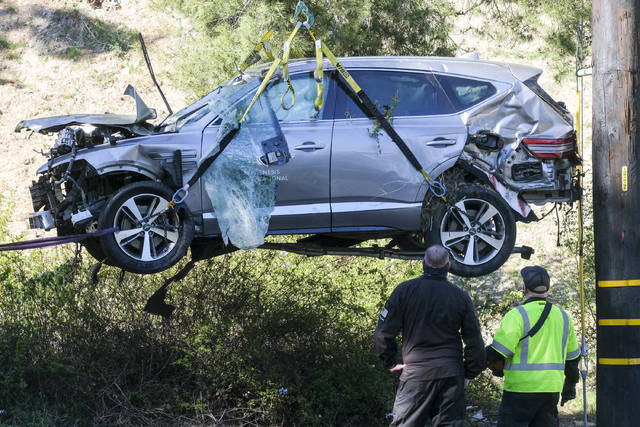 FILE - In this Feb. 23, 2021, file photo, a crane is used to lift a vehicle following a rollover accident involving golfer Tiger Woods, in the Rancho Palos Verdes suburb of Los Angeles. Authorities said Wednesday, April 7, Woods was speeding when he crashed leaving him seriously injured. (AP Photo/Ringo H.W. Chiu, File)