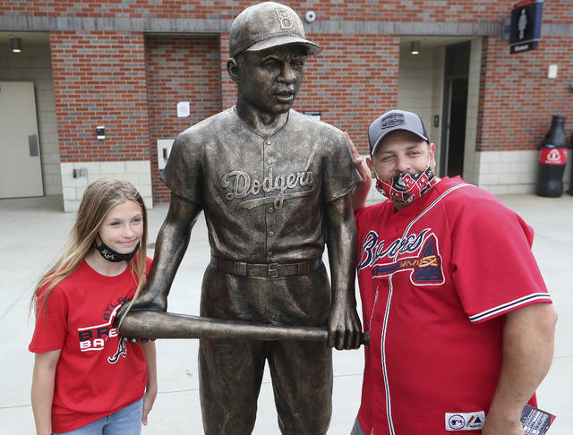 Atlanta Braves fans Pete Ciccarello and his daughter Haley pause for a photo with the statue of Jackie Robinson on Jackie Robinson Day prior to a baseball game between the Miami Marlins and Atlanta Braves in Atlanta, Thursday, April 15, 2021. (Curtis Compton/Atlanta Journal-Constitution via AP)