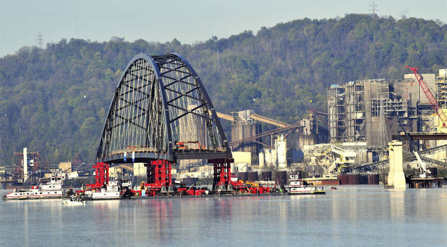 Crews with Flatiron Construction move an 830-foot long tied arch span on the barges on the Ohio River, Monday, April 26, 2021, as part of the construction process of the Wellsburg Bridge. The bridge will eventually link Wellsburg, West Virginia, with Brilliant, Ohio. The tied arch span is estimated to weigh 9 million pounds, or 4,100 tons. (Scott McCloskey/The Intelligencer via AP)