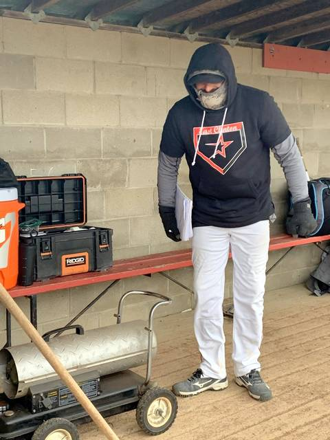 East Clinton head coach Brian Carey keeps warm next to a heater durng Thursday's game with Hillsboro at ECHS. (Photo by Melony Arnold)