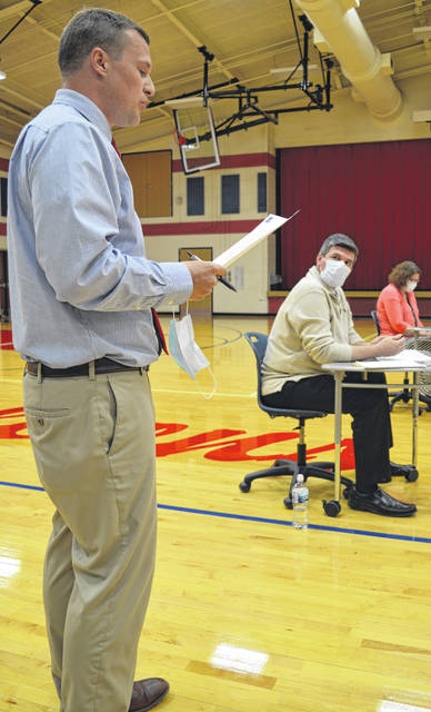 Clinton-Massie High School Principal Aaron Seewer, left foreground, delivers his report to the school board. In the background are Superintendent Matt Baker and Treasurer Carrie Bir.