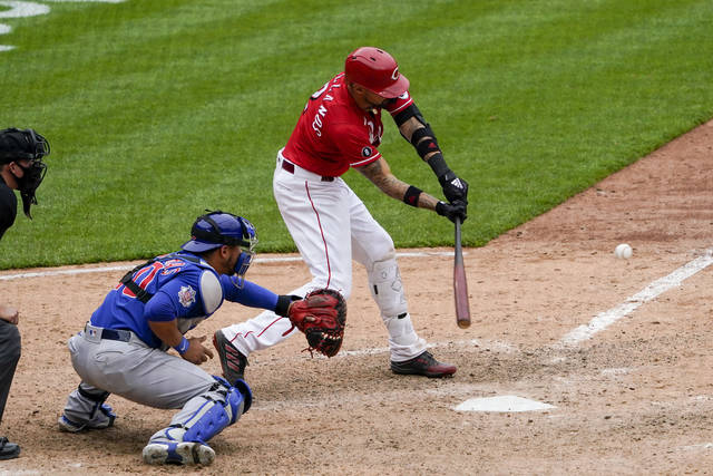 Cincinnati Reds' Nick Castellanos (2) hits a walkoff RBI single in the 10th inning during a baseball game against the Chicago Cubs in Cincinnati on Sunday, May 2, 2021. (AP Photo/Jeff Dean)