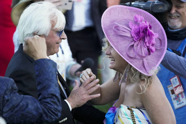 CORRECTS PERSON AT RIGHT TO LEONA O'BRIEN - Trainer Bob Baffert is greeted by Leona O'Brien, wife of jockey John Velazquez, after Medina Spirit won the 147th running of the Kentucky Derby horse race at Churchill Downs, Saturday, May 1, 2021, in Louisville, Ky. (AP Photo/Jeff Roberson)