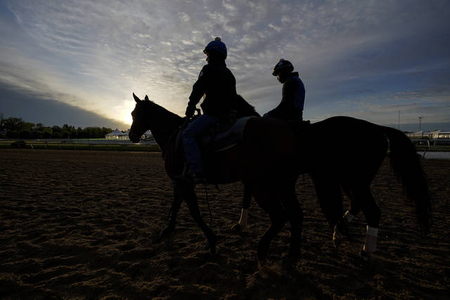 Preakness entrant Midnight Bourbon, right, walks on the track during a training session ahead of the Preakness Stakes horse race at Pimlico Race Course, Wednesday, May 12, 2021, in Baltimore. (AP Photo/Julio Cortez)