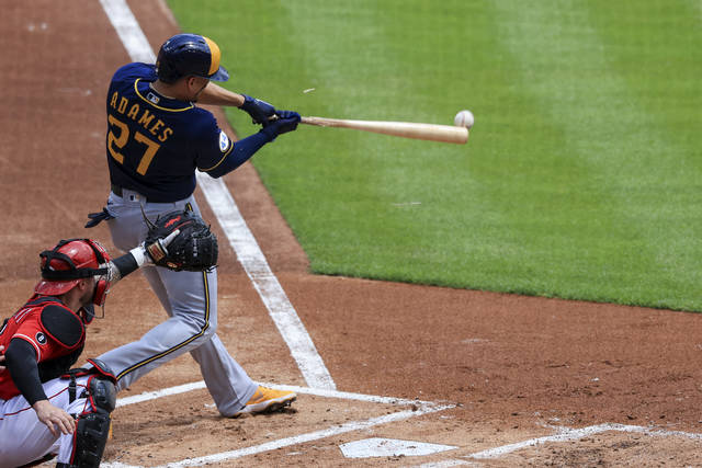 Cincinnati Reds' Tucker Barnhart, left, protects home plate as Milwaukee Brewers' Willy Adames (27) hits a two-run RBI-single during the first inning of a baseball game in Cincinnati, Sunday, May 23, 2021. (AP Photo/Aaron Doster)