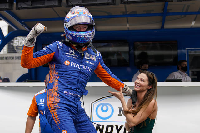 Scott Dixon, front left, of New Zealand celebrates after winning the pole during qualifications for the Indianapolis 500 auto race as his wife Emma Davies-Dixon, right, watches at Indianapolis Motor Speedway in Indianapolis, Sunday, May 23, 2021. (AP Photo/Michael Conroy)