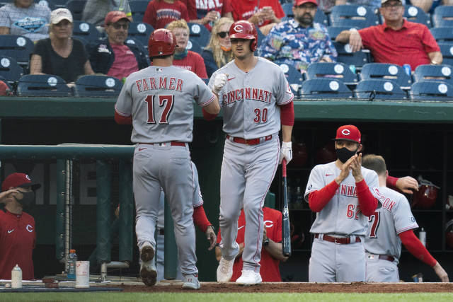 Cincinnati Reds' Kyle Farmer (17) is congratulated by Tyler Mahle (30) after hitting a home run during the third inning of the team's baseball game against the Washington Nationals in Washington, Tuesday, May 25, 2021. (AP Photo/Manuel Balce Ceneta)