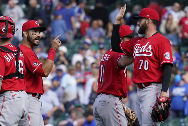 Cincinnati Reds relief pitcher Tejay Antone, right, celebrates with teammates Eugenio Suarez, second from left, and Kyle Farmer after they defeated the Chicago Cubs in a baseball game in Chicago, Sunday, May 30, 2021. (AP Photo/Nam Y. Huh)