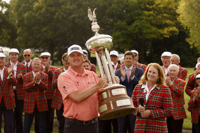 Jason Kokrak poses with the Leonard Trophy after winning the Charles Schwab Challenge golf tournament at the Colonial Country Club in Fort Worth, Texas Sunday, May 30, 2021, as Colonial Country Club president Christine Klote, right, and other applaud him.(AP Photo/Michael Ainsworth)