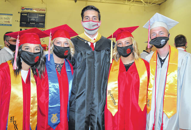 Just minutes prior to the commencement ceremony are four new East Clinton graduates and a high school teacher. From left are Marci Ellis, Lanie Clark, social studies teacher Phillip Shori, Jericka Boggs, and Carter Carey.