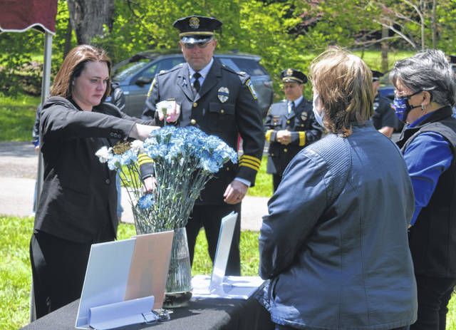 Michelle Lagore, far left, lays a flower in memory of her husband Jason Lagore during the Peace Officers Memorial Day ceremony at Sugar Grove Cemetery on Monday. Jason Lagore was the Ohio Department of Natural Resource officer who died earlier this year while attempting to rescue a teen that fell through the ice.