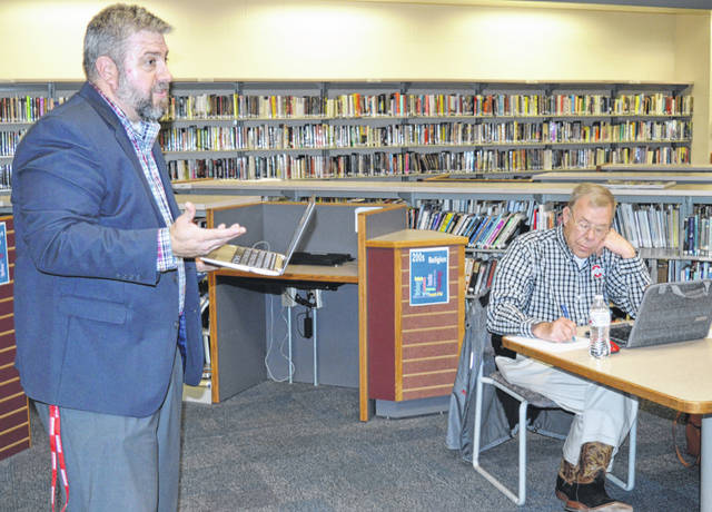 East Clinton High School Principal Michael Adams was awarded a new two-year contract this week. Here he updates the school board in the library on Monday, East Clinton's last day of school. Board member Dr. Robert Carey takes notes.
