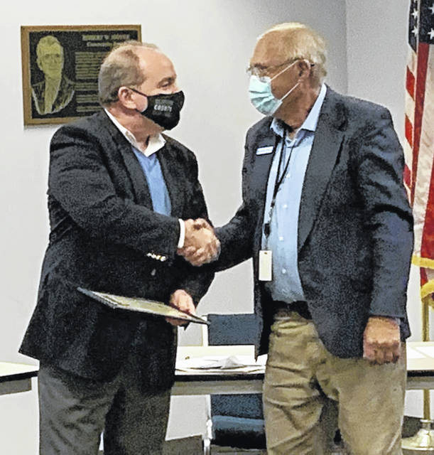 """Mayor John Stanforth, right, shakes hands with Dan Evers after presenting him with a proclamation for Economic Development Week at Thursday's Wilmington City Council meeting. Evers is executive director of the Clinton County Port Authority, one of the entities cited by Stanforth as responsible for economic development in the county. Stanforth also called Evers a """"vital asset"""" to the community."""