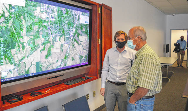 Prior to this week's Wilmington City Planning Commission meeting, Clinton County Regional Planning Commission Executive Director Taylor Stuckert, left foreground, and City Planning Commission member David Hockaday, right foreground, talk in front of a large video screen.